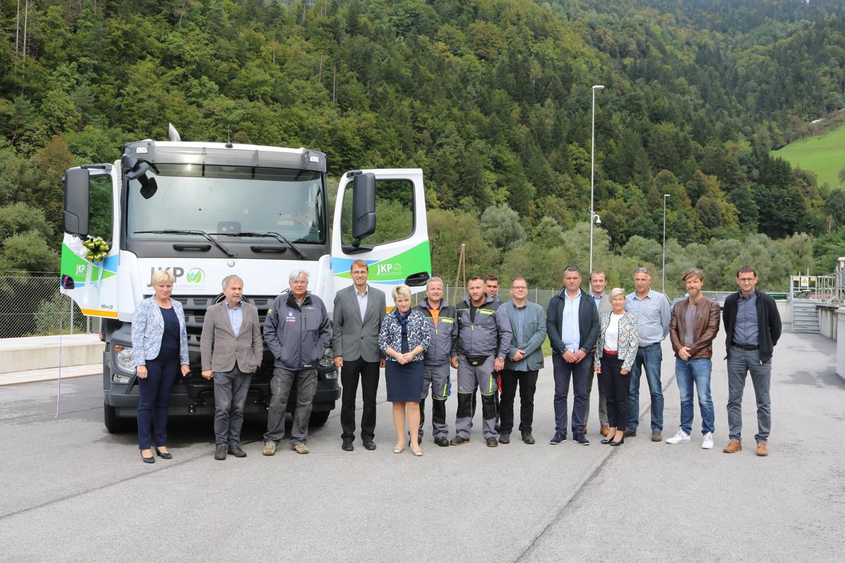 Udeleženci slovestne predaje stojijo pred novim tovornim vozilom za praznjenje greznic