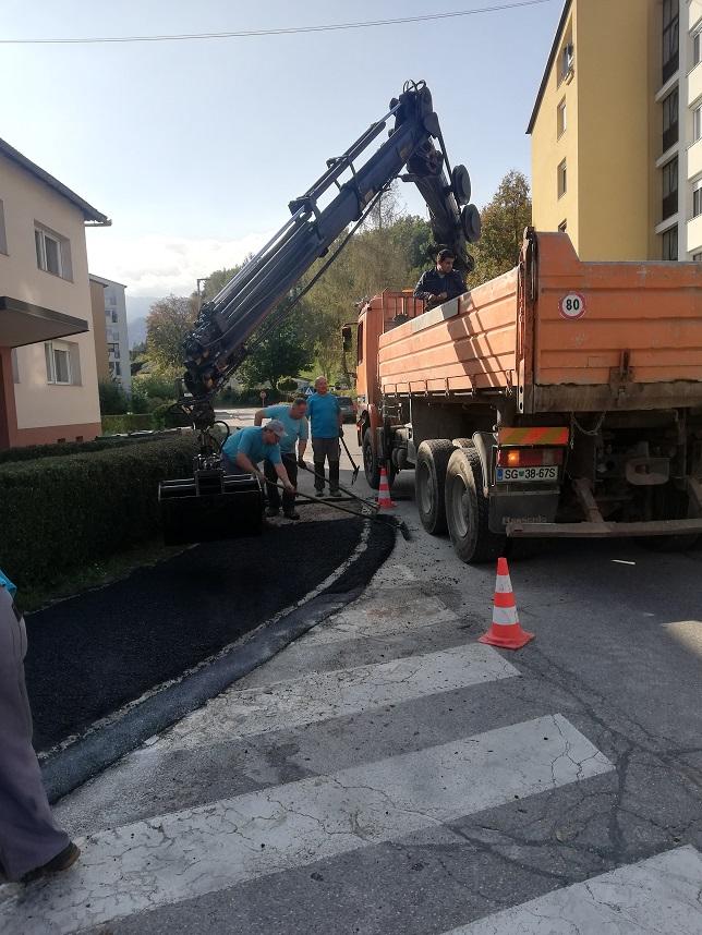 Tovornjak z asfaltno mešanico napisa material na cesto