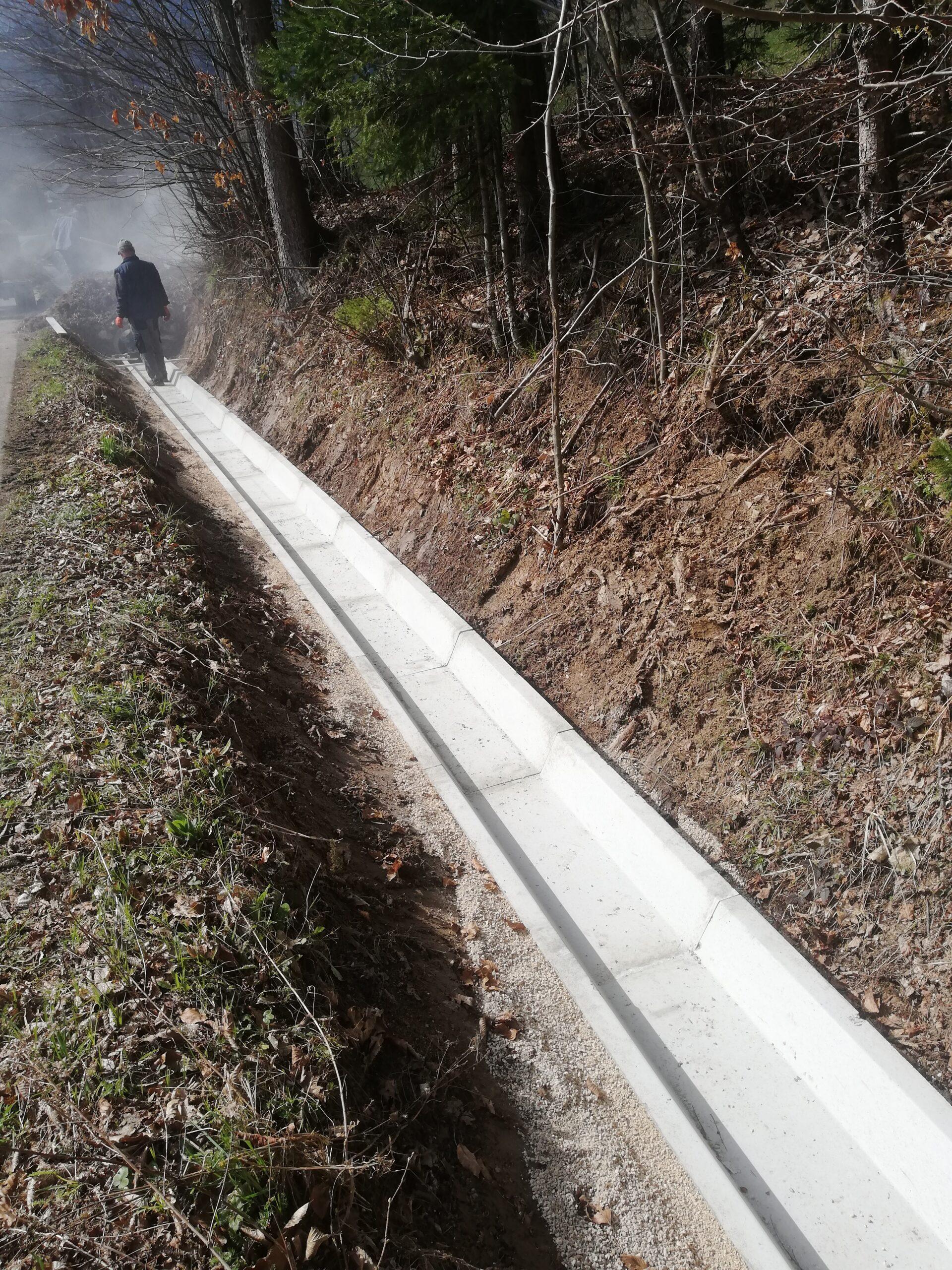 Delavec nadzuruje nasipanje materila za novo betonsko kanaleto