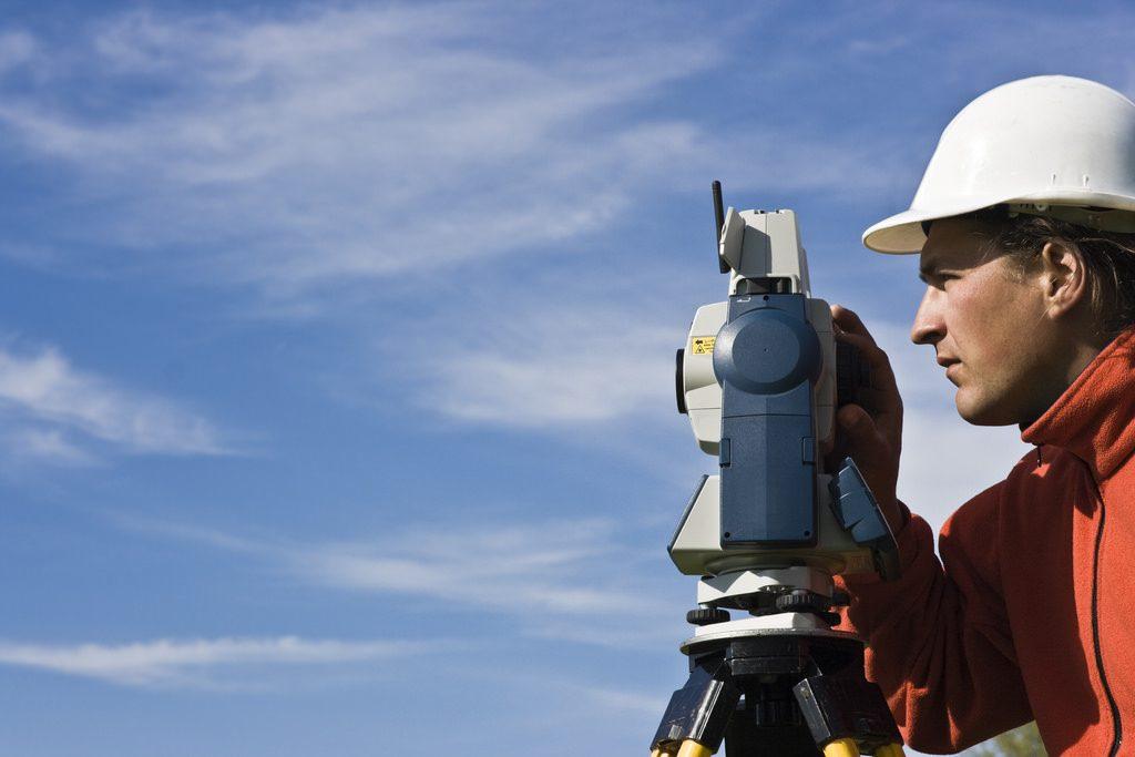 Geodet na terenu opravlja meritev z geodetsko napravo