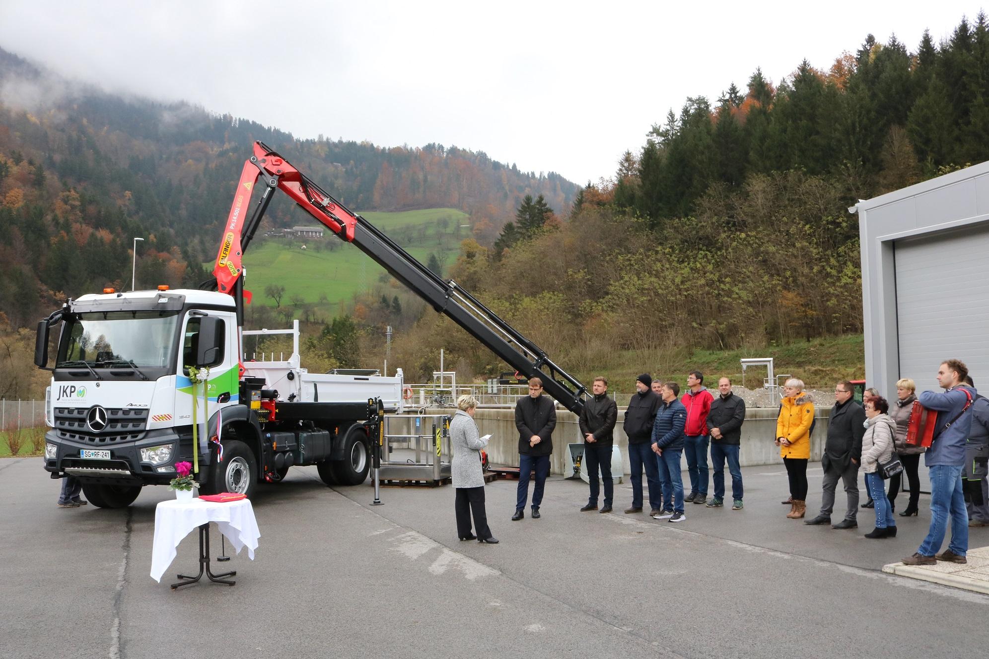 Direktorica Andreja Jehart stoji ob novem tovornem vozilu in nagovarja udeležence slovesne predaje