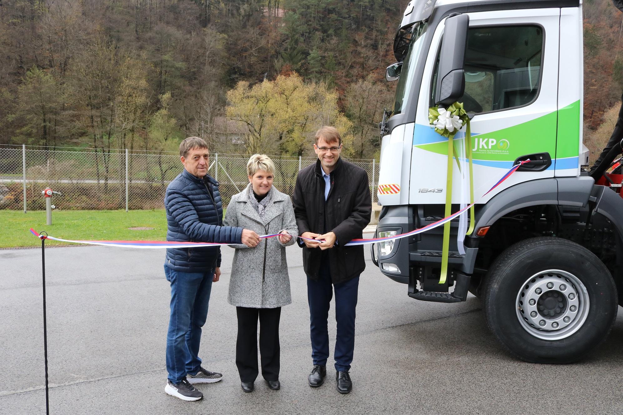 Direktorica Andreja Jehart, župan Tomaž Rožen in predsednik nadzornega sveta Roman Krivograd režejo sloestni trak ob predaji novega tovornega vozila