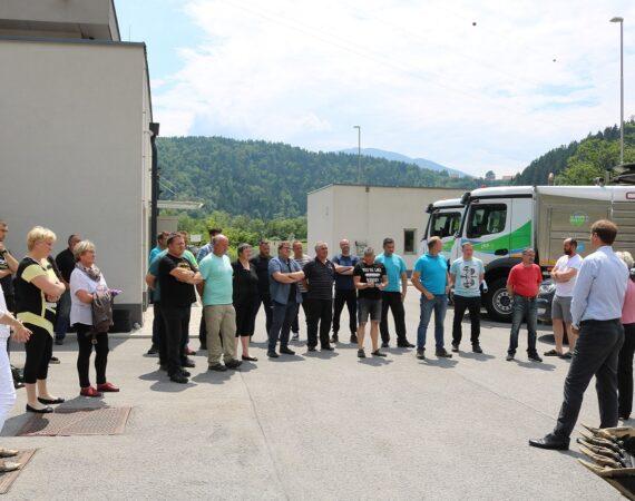 Udeleženci slovesne predaja delovnega stroja poslušajo govornika